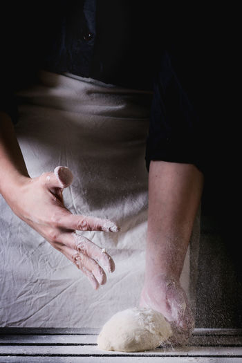 Midsection of person kneading dough