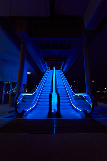 Empty illuminated escalator under bridge