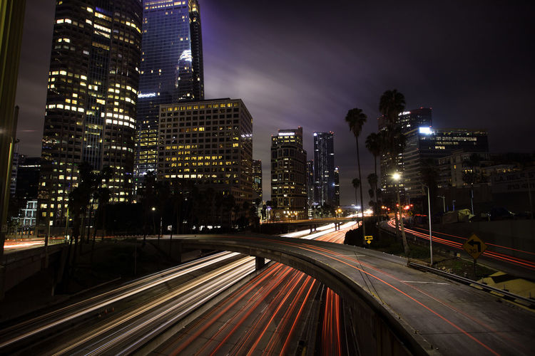 Light Trails On Road Amidst Illuminated Buildings In City At Night