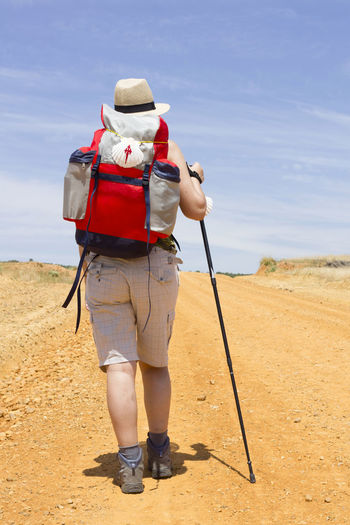 Rear view of hiker in hat with backpack walking on dirt road during sunny day