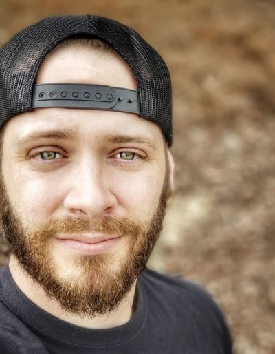 Close-up portrait of bearded man in cap outdoors