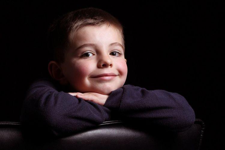 Portrait of cute baby boy against black background