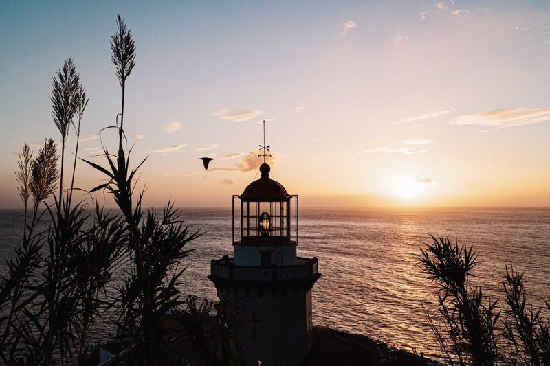 Silhouette lighthouse by sea against sky during sunset