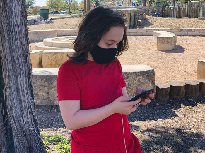 Full length of woman using phone while standing outdoors
