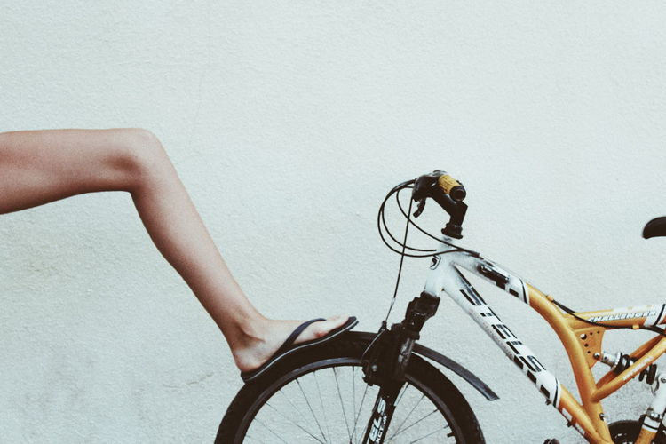 Low section of woman with bicycle against wall