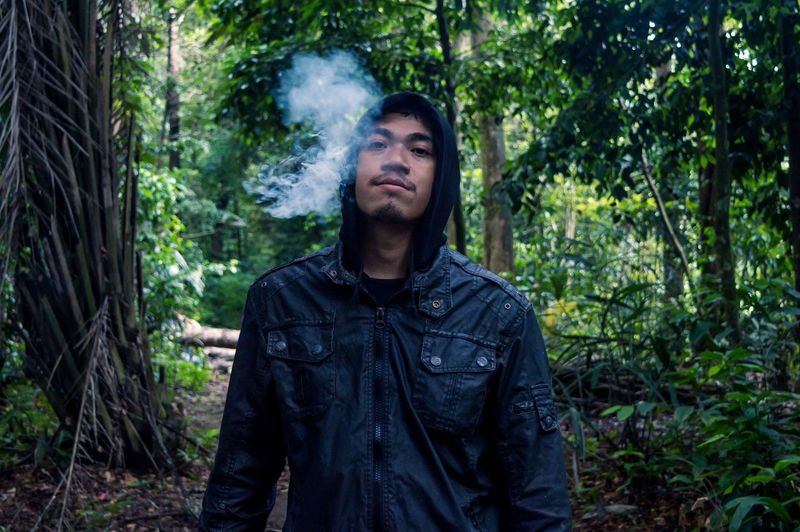 Portrait of man exhaling smoke in forest