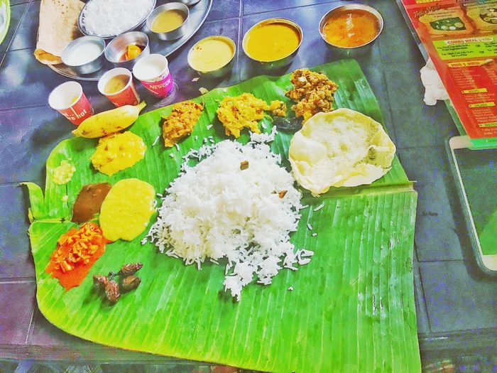 Amazing #sadya Kerala traditional feast served on banana leaf on way to #munnar from #Cochin at #Saddya restaurant. Food is little but spicy but very tasty. One should definitely experience this when traveling to munnar Sadhya (Malayalam: സദ്യ) is a feast consisting of a variety of traditional vegetarian dishes usually served on a banana leaf in Kerala, India.Sadhya means banquet in Malayalam. It is a vegetarian feast prepared by both, men and women, especially when needed in large quantities, for weddings and other special events. . . Food is eaten with the right hand, without cutlery. The fingers are cupped to form a ladle. A normal Sadhya can have about 24–28 dishes served as a single course. . . The main dish is plain boiled rice, served along with other dishes collectively called #Kootan which include curries like #parippu,sambar, #rasam, #pulisseri and others like #kaalan, avial, thoran, olan, pachadi, kichadi, koottukari, erissery, #mangopickle, #pulinji, #narangaachaar (lime pickle), as well as papadam, #plantain chips, sharkara upperi, banana, plain curd and buttermilk. India Indian Culture  Indian Food Kerala Kerala Food Sadhya Freshness High Angle View Food And Drink Food Still Life No People Healthy Eating