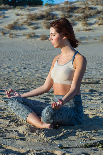 Young Woman Meditating In Lotus Position At Beach