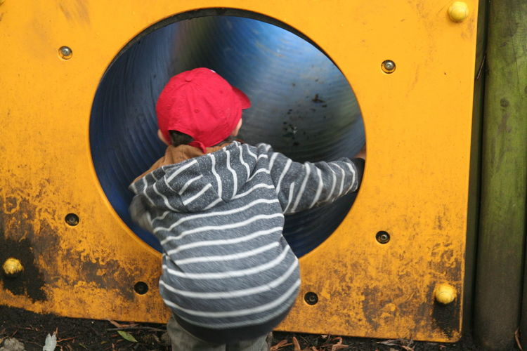 Rear view of a boy looking in tunnel