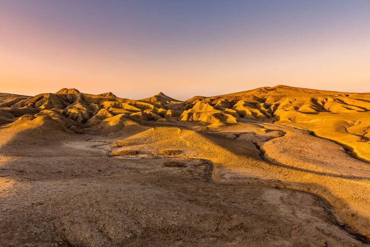 Scenic view of arid landscape against sky during sunset