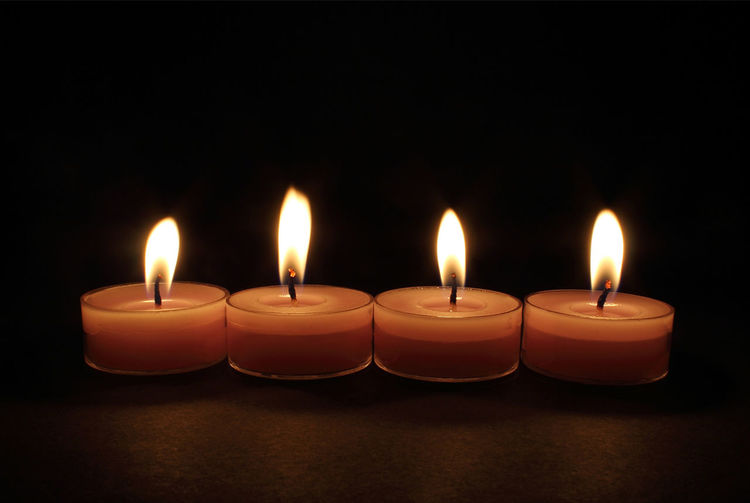 Candles on a black isolated background. Isolated Black Background Burning Candle Close-up Flame Heat - Temperature Illuminated Indoors  No People Still Life Still Life Photograpy