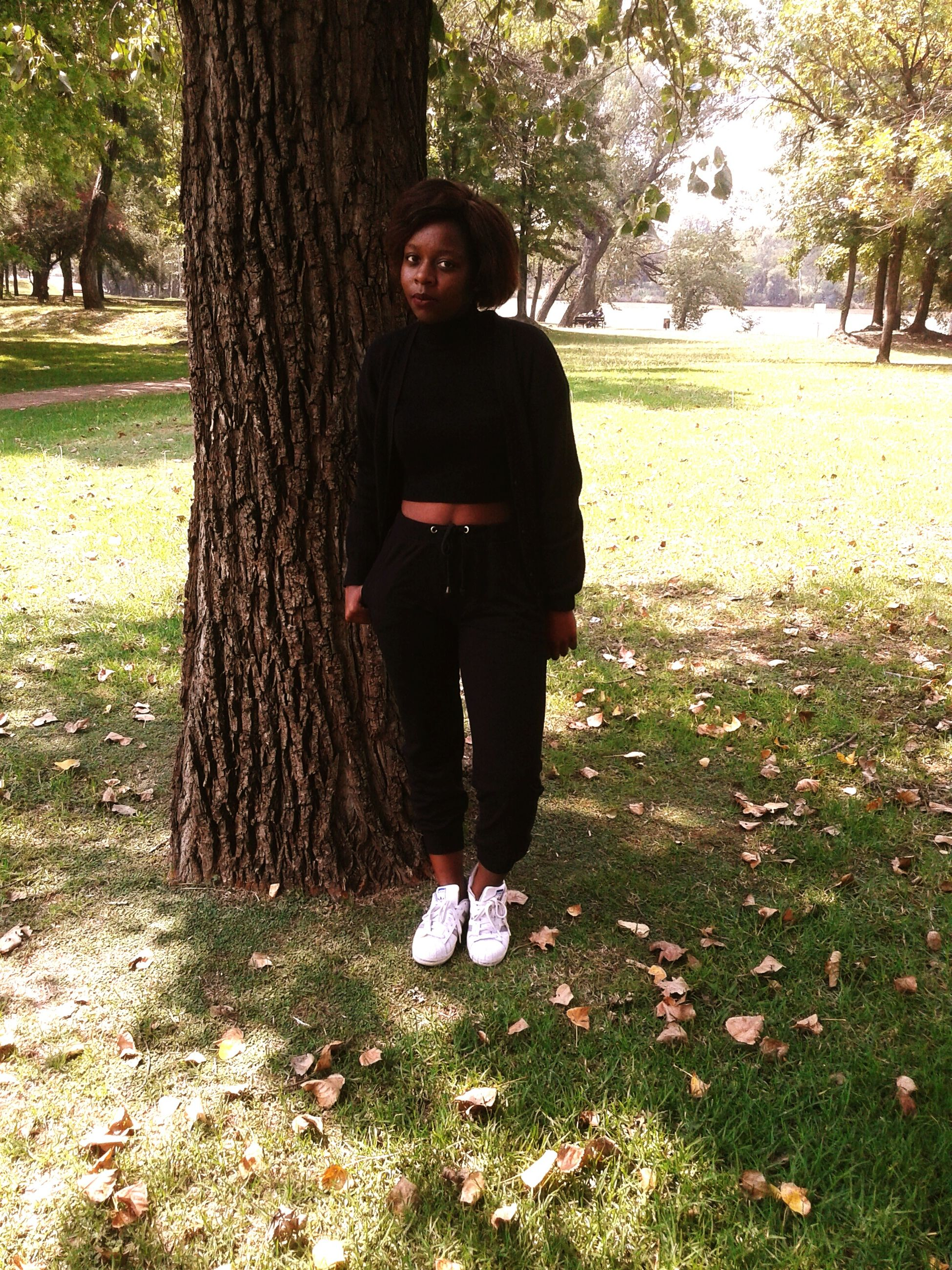 tree, tree trunk, lifestyles, front view, young adult, person, casual clothing, standing, looking at camera, leisure activity, forest, portrait, young women, full length, grass, three quarter length, park - man made space, nature