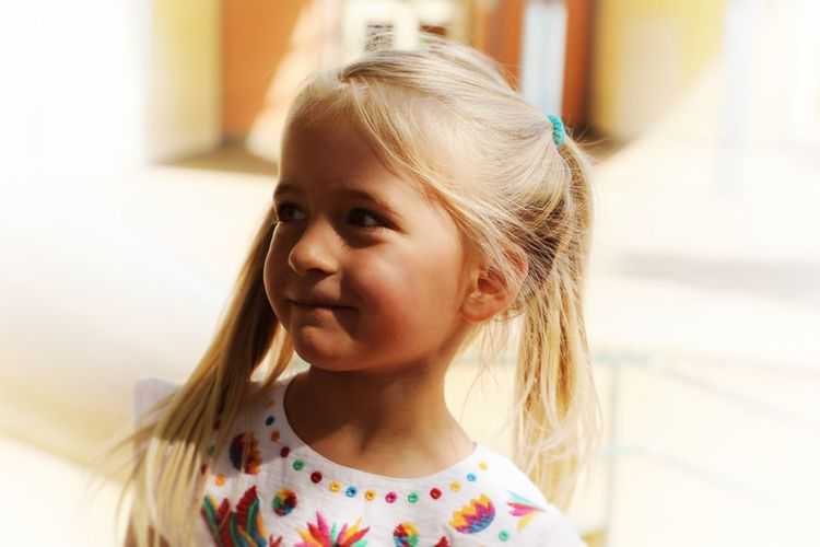 4 year old blonde girl with angelic smile in miday sun