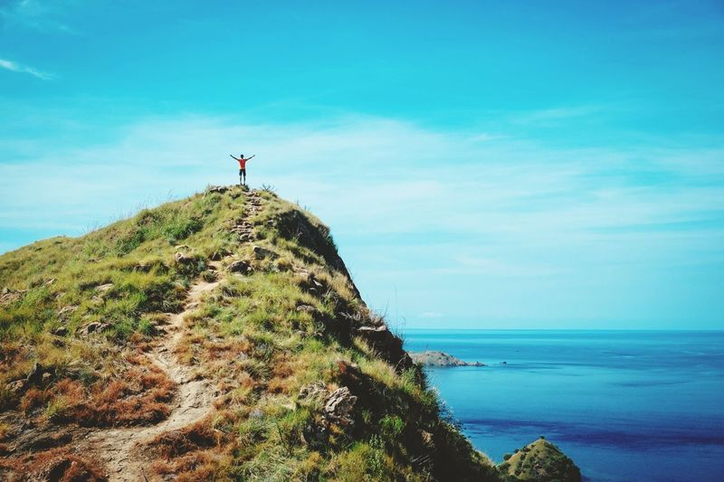 Man Standing On Top Of Cliff Against Blue Sky