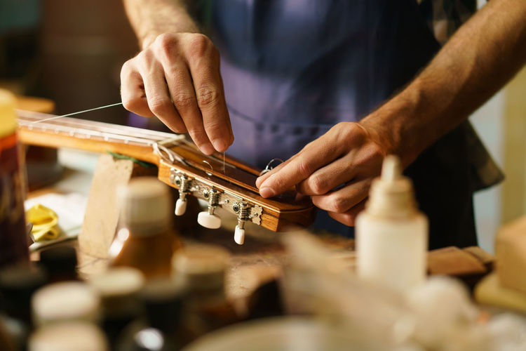 Midsection of man preparing guitar in workshop