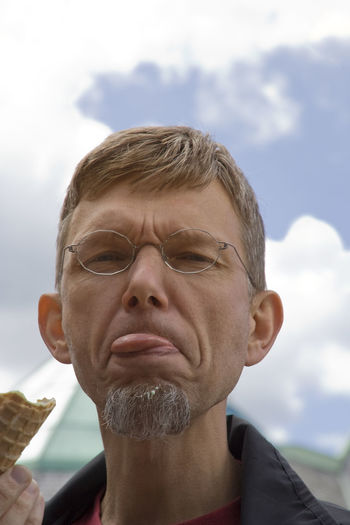 Portrait of mature man sticking out tongue against sky