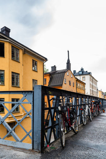 Bicycles on street by buildings against sky