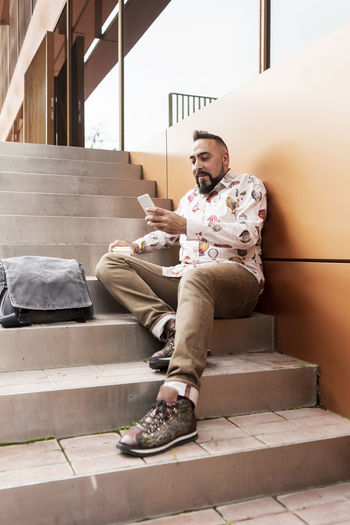 Young man using smart phone while sitting on staircase