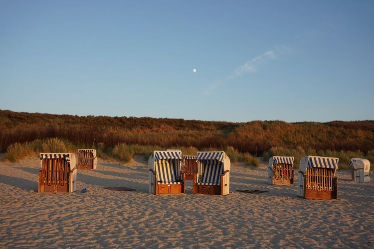 Hooded Beach Chairs On Sand Against Blue Sky During Sunset