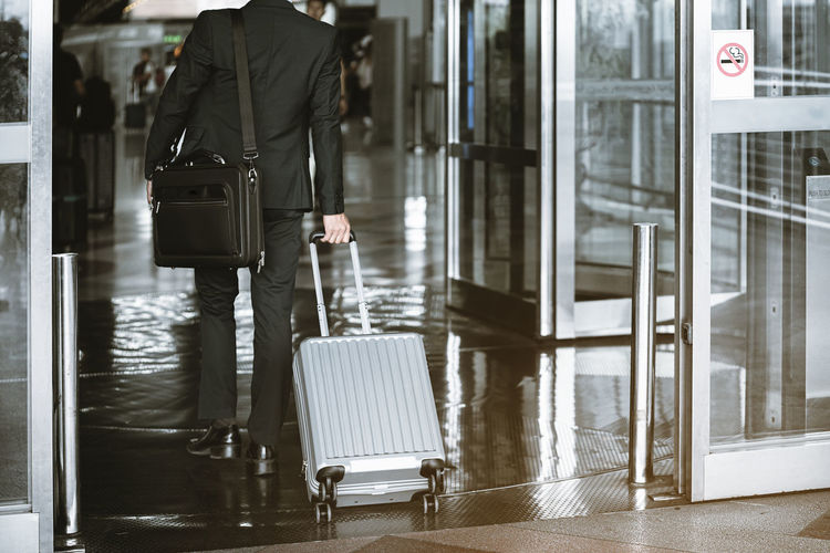 Man with umbrella standing at airport