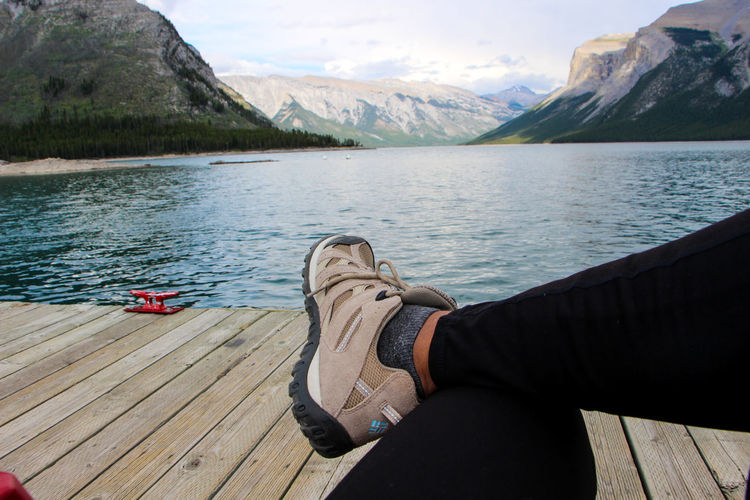 Low section of man relaxing on wooden pier at lake