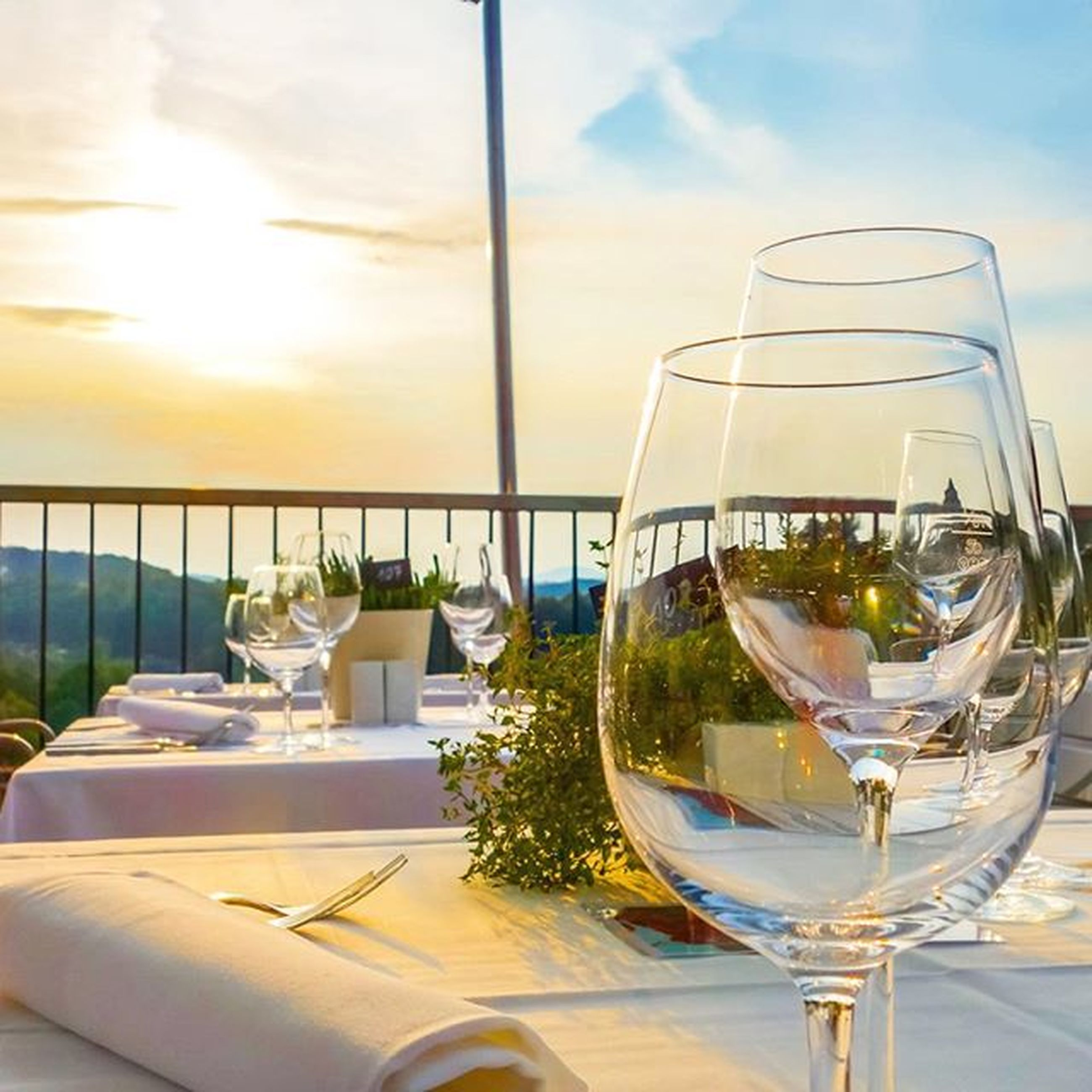 table, glass - material, sky, sea, drink, transparent, restaurant, drinking glass, window, chair, indoors, sunlight, food and drink, water, horizon over water, glass, wineglass, cloud - sky, refreshment, day