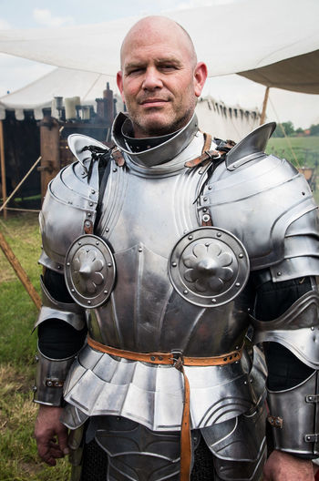 Portrait of man in knight costume standing on field during festival