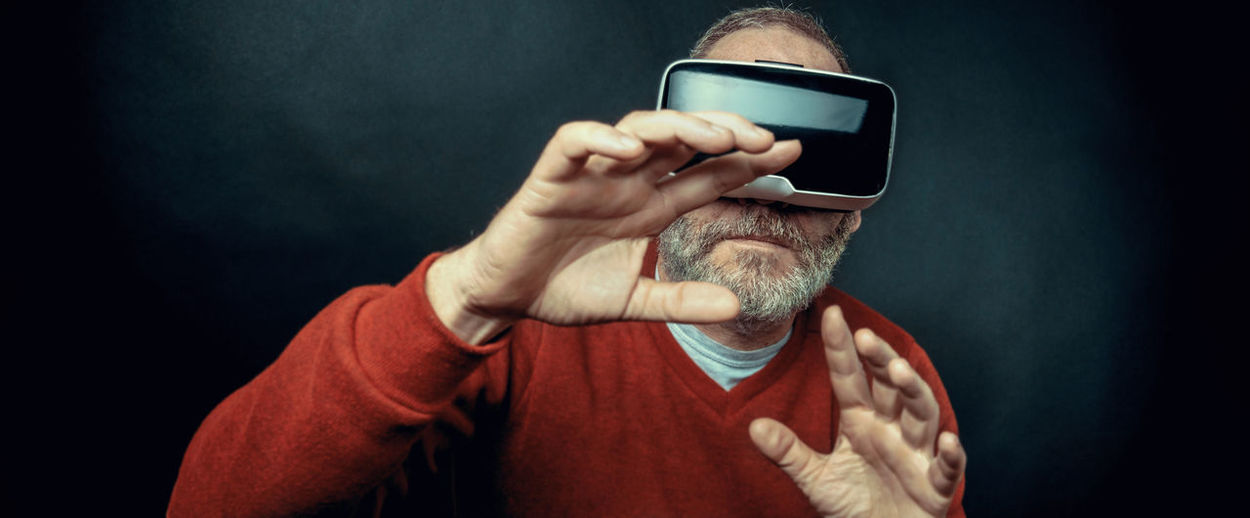 Panoramic view of senior man using virtual reality headset against black background