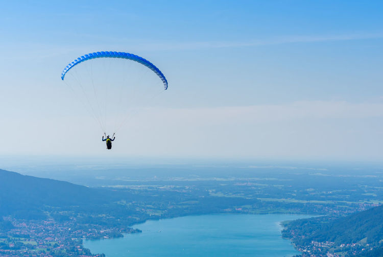 Full length of man paragliding over lake against blue sky