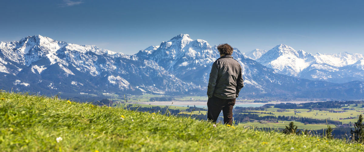 Man Standing On Grassy Field Against Snowcapped Mountains