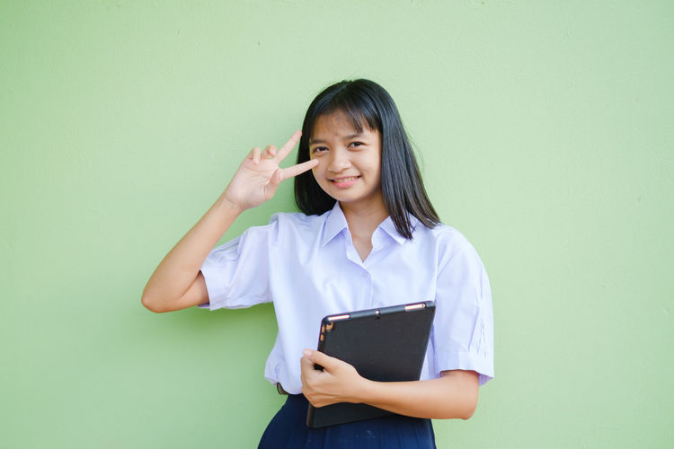 Smiling young woman standing against wall
