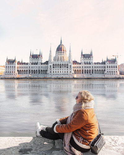 Woman in warm clothes sitting by river against historic building