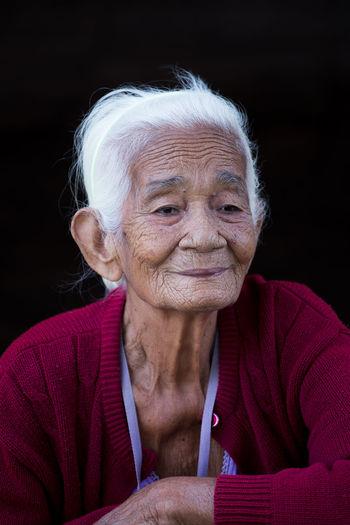 Smiling Senior Woman Looking Away Against Black Background