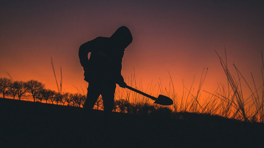 Sunset Sky Silhouette Real People One Person Nature Orange Color Land Men Field Standing Leisure Activity Holding Plant Lifestyles Beauty In Nature Outdoors Grass Shovel Graveyard Grave Digging Digital Trees Night Dead Death Breathtaking Outstanding Grass Moored