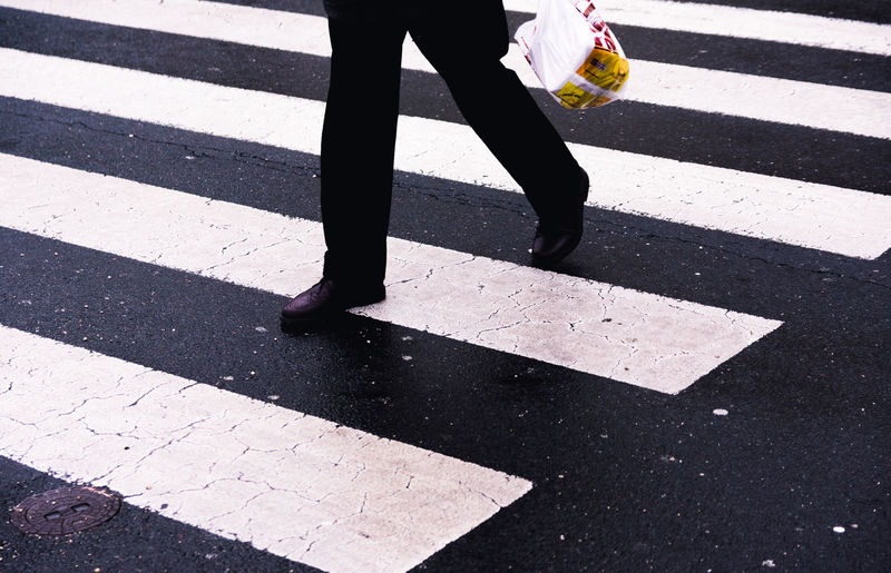 Low section of person walking on zebra crossing