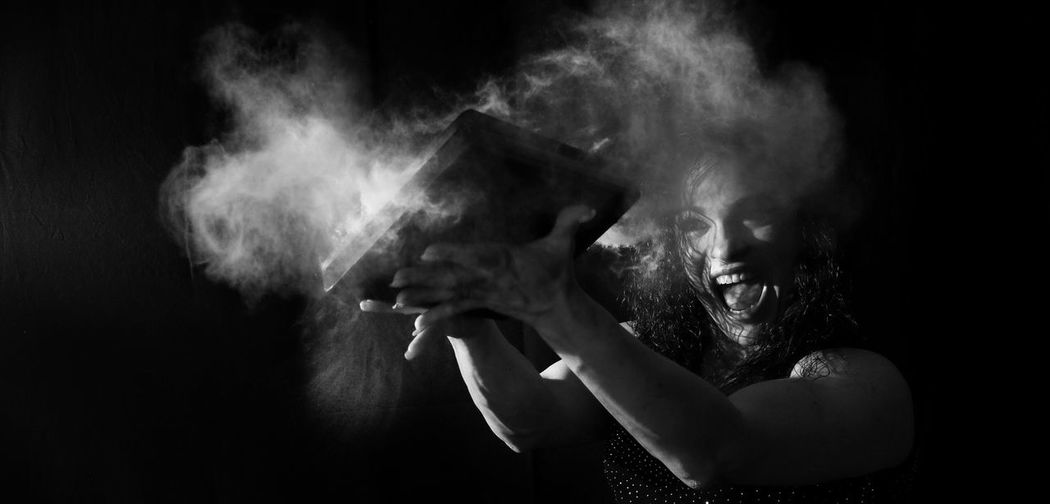 Woman playing with book against black background