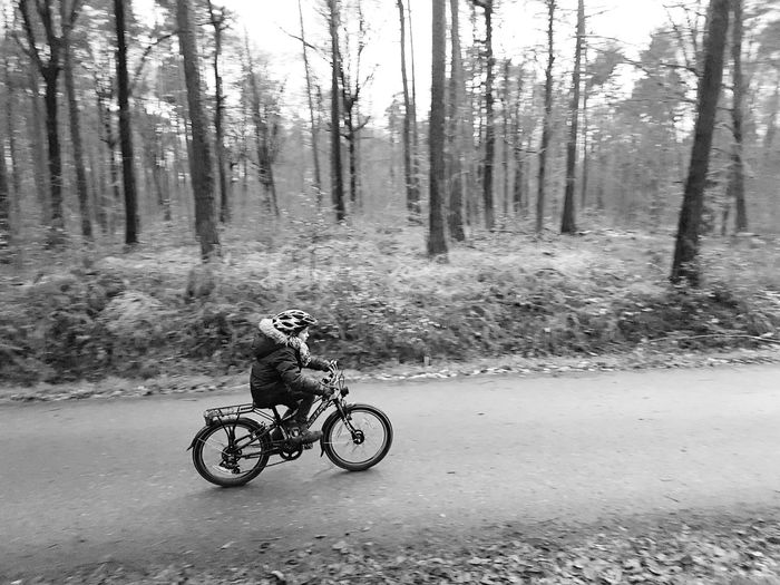 Girl cycling on road against trees at forest