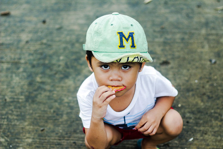 Portrait of boy eating food while crouching on road