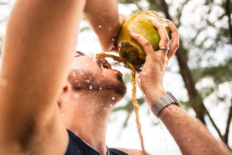 Low angle view of man drinking coconut water