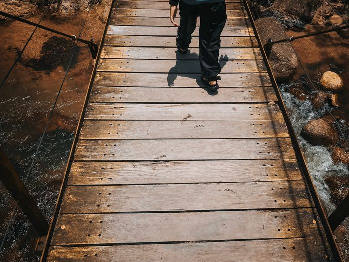 Boy walk through a wooden bridge at the riverside Low Section Human Leg Real People Body Part One Person Footpath Lifestyles Day Shoe High Angle View Walking Sunlight Leisure Activity Standing Men Shadow Human Body Part Nature Outdoors Human Limb