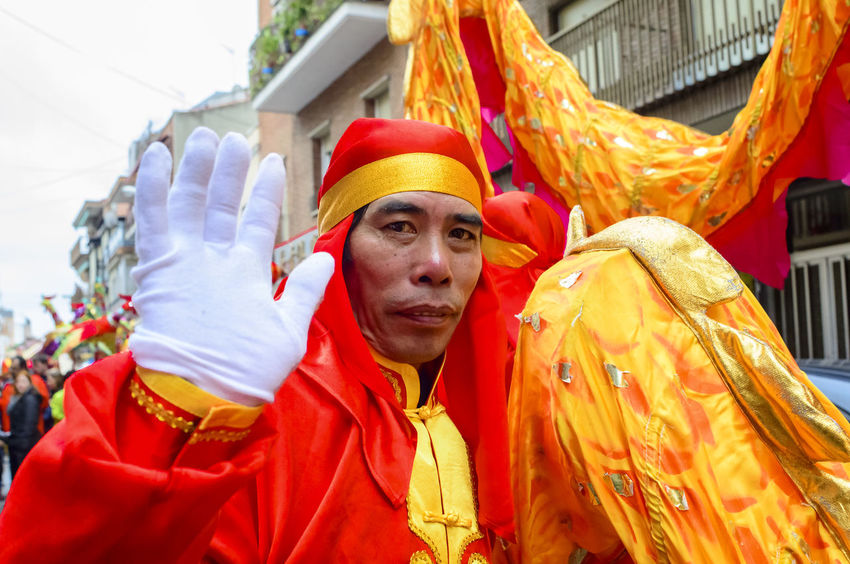 A Chinese man from the red dragon team waving and looking at the camera. The Chinese community in Madrid celebrated the Chinese New Year of the Monkey in the Usera district of Madrid, Spain. Celebration Chinese Chinese Holiday Chinese New Year Chinese New Year 2016 Colours Composition Culture Cultures Editorial  Front View Happy Holding Looking At Camera Man Parade People Person Perspective Portrait Real People Red Standing Waving Year Of The Monkey