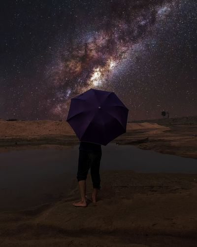 One men with an umbrella standing on the bank of a river on a under the sky full of star