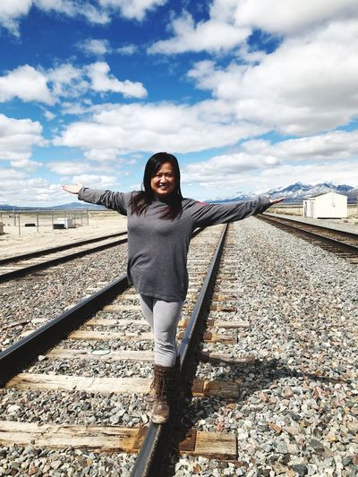 Portrait of smiling woman balancing on railroad track against sky