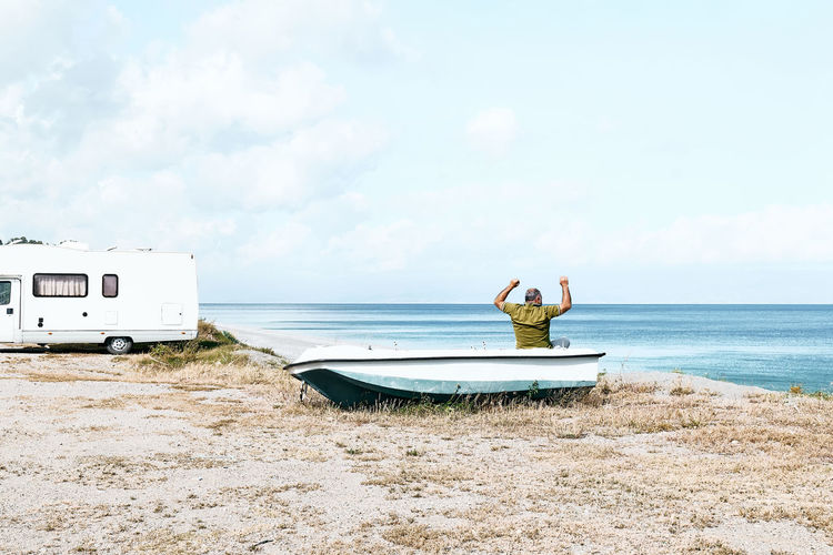Man sitting in boat on the beach near his white camper van parked by the sea. sicily. ionian sea.