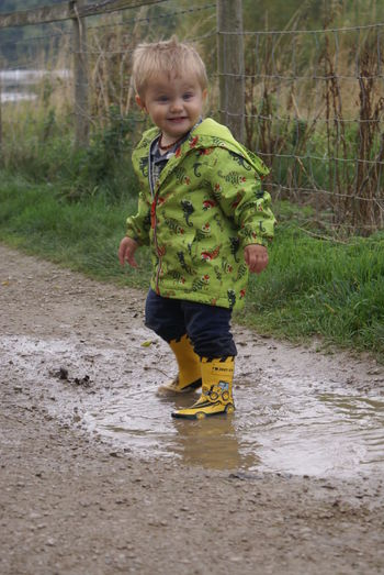 Boy playing in puddle on pathway