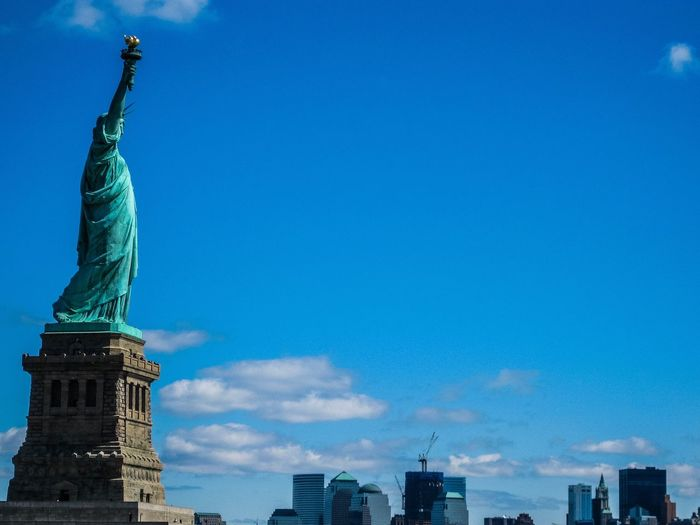 Statue of liberty against blue sky during sunny day