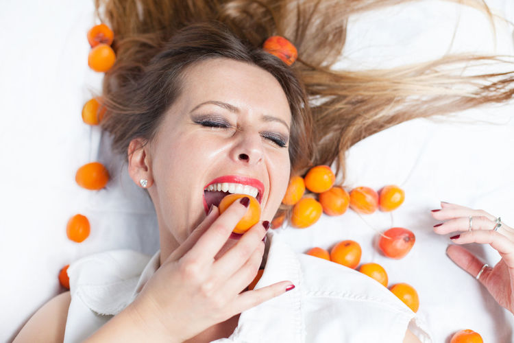 Directly above shot of young woman eating fruit while lying on white background