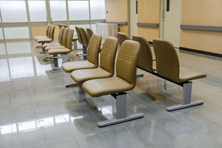 Empty chairs against tiled floor