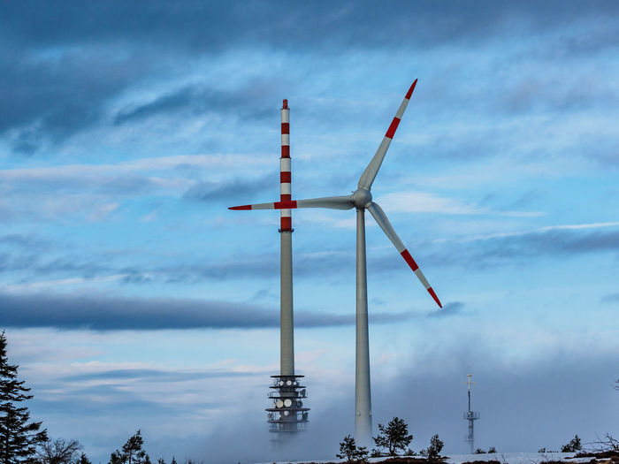 Low angle view of windmills against sky