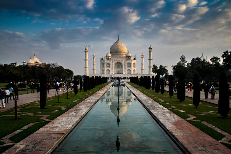 Reflection of taj mahal on reflecting pool against cloudy sky
